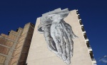 A mural close to Omoneia Square, comissioned by the municipality and realised by students of the Athens School of fine Arts, shows the famous hands by Albrecht Dürer pointing down towards the city Photo: Julia Tulke/aestheticsofcrisis.org